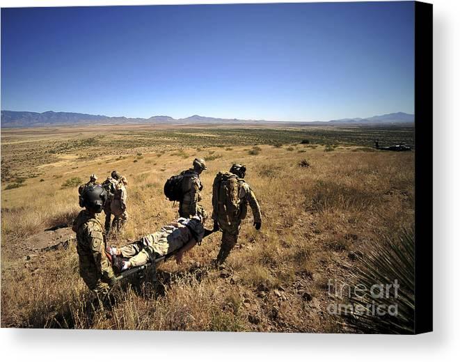 Men Canvas Print featuring the photograph U.s. Air Force Pararescuemen Carry by Stocktrek Images