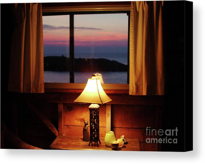 View Out Cottage Window To Sunset On Ocean In Late Spring. Room Lit By Table Lamp From The 1950's. On Monhegan Island In Maine. Canvas Print featuring the photograph Night View by Georgia Sheron