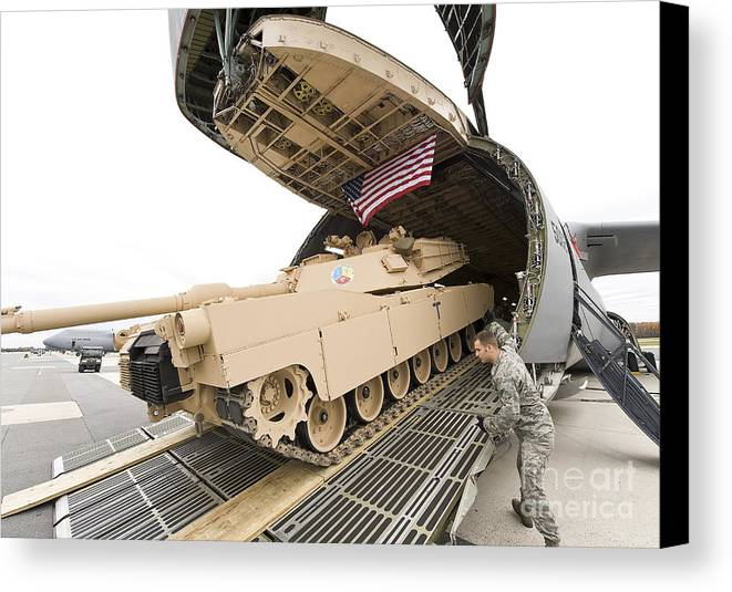 Tank Canvas Print featuring the photograph Airmen Load A Tank Into A C-5m Super by Stocktrek Images
