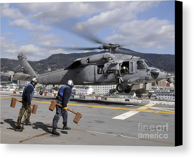 Chocks Canvas Print featuring the photograph Airmen Prepare To Chock And Chain An by Stocktrek Images