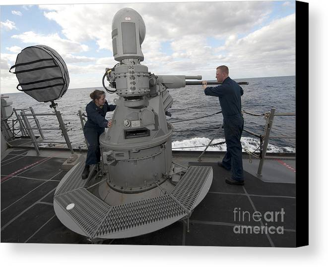 Military Canvas Print featuring the photograph Sailors Conduct Maintenance On The Mk38 by Stocktrek Images