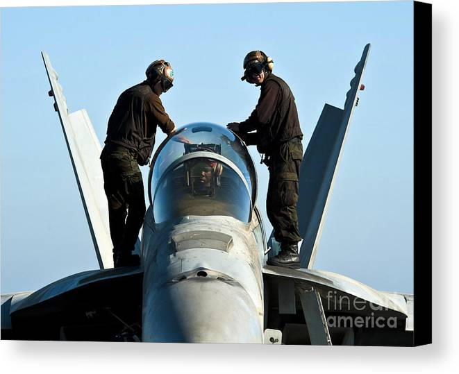 Operation Enduring Freedom Canvas Print featuring the photograph U.s. Navy Sailors Wipe Down The Canopy by Stocktrek Images