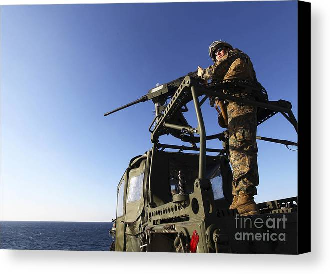 Camouflage Clothing Canvas Print featuring the photograph A Machine Gunner Mounts A M-2 by Stocktrek Images