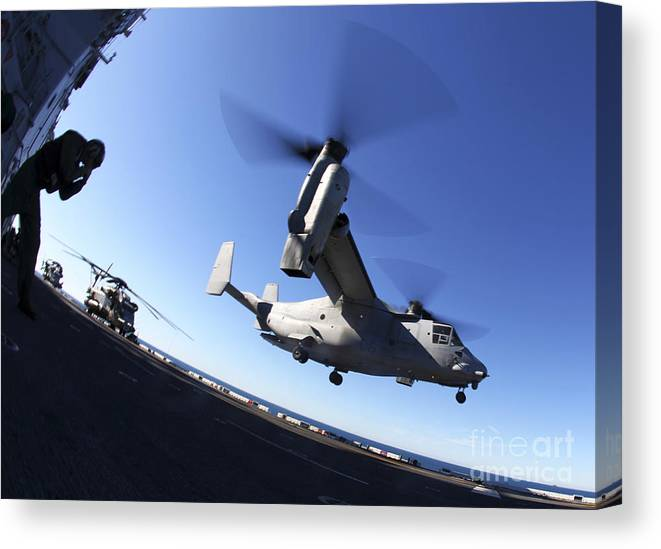 Warship Canvas Print featuring the photograph An Mv-22 Osprey Lands Aboard The Uss by Stocktrek Images