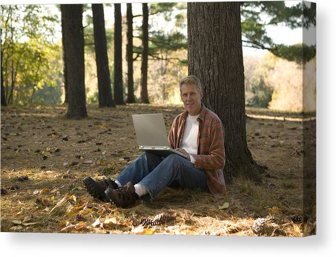 People Canvas Print featuring the photograph Man using laptop outdoor by Comstock Images