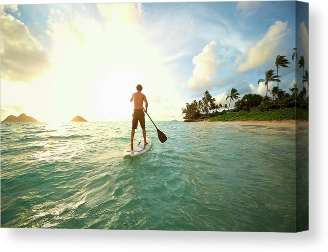 Tranquility Canvas Print featuring the photograph Caucasian Man On Paddle Board In Ocean by Colin Anderson Productions Pty Ltd