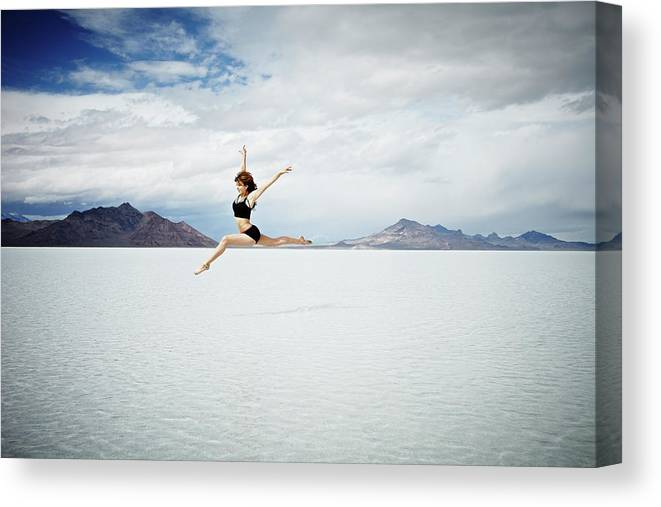 Ballet Dancer Canvas Print featuring the photograph Ballerina Leaping In Mid-air Over Lake by Thomas Barwick