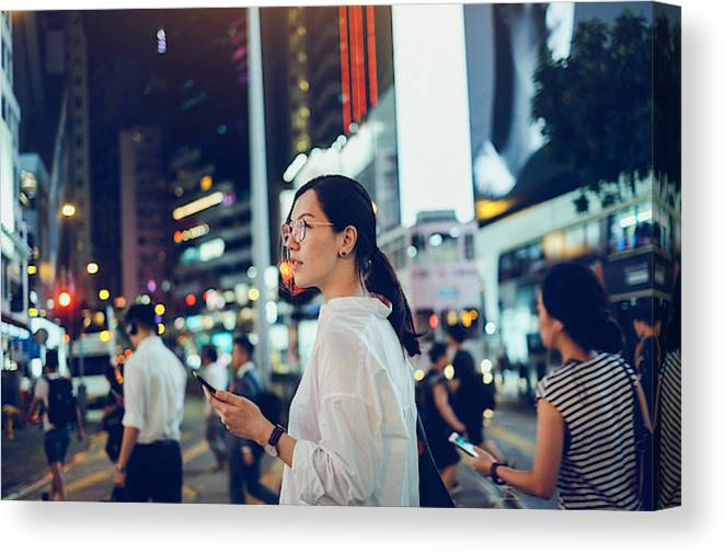 Financial Building Canvas Print featuring the photograph Beautiful Asian woman using mobile phone while crossing road in busy downtown city street at night by D3sign