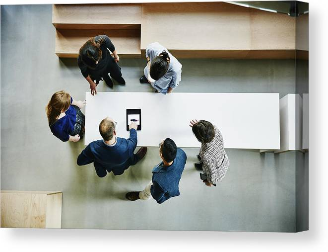 Expertise Canvas Print featuring the photograph Business colleagues discussing project in office by Thomas Barwick