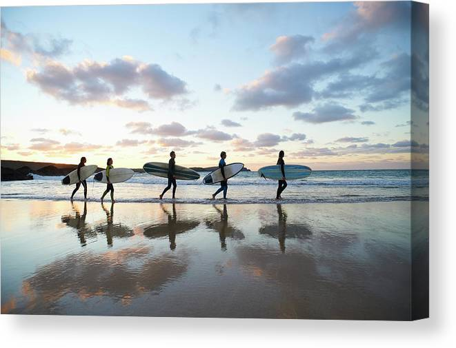Young Men Canvas Print featuring the photograph Five Surfers Walk Along Beach With Surf by Dougal Waters