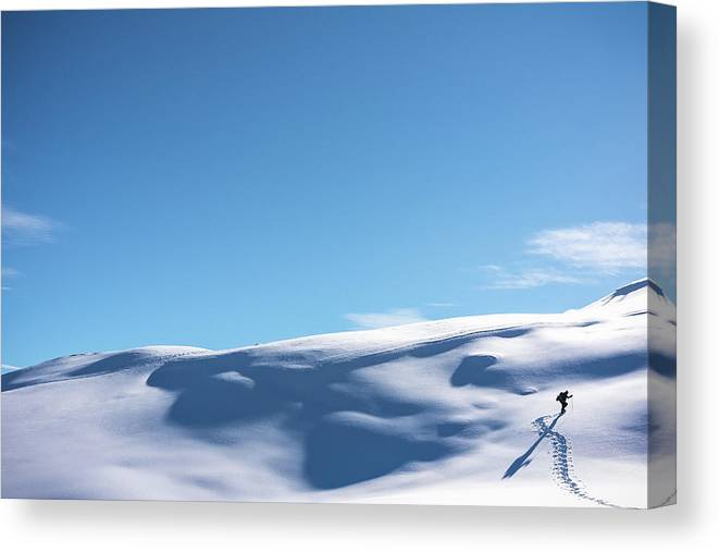 Extreme Terrain Canvas Print featuring the photograph Hiker Walking Up Snowy Hillside by Deimagine