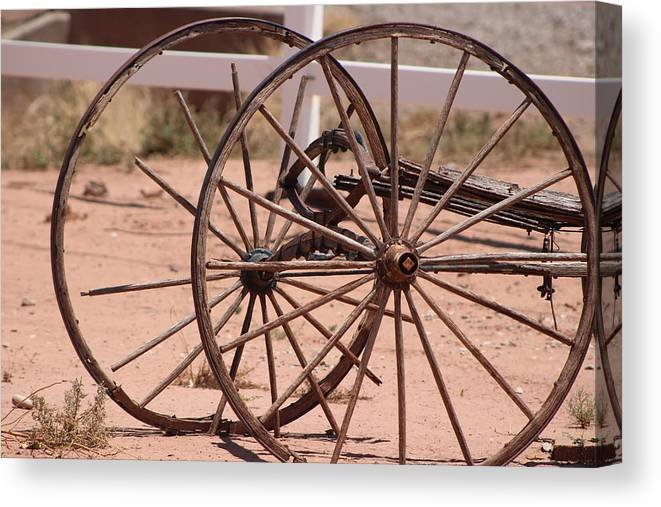 Old Wagon Wheel Canvas Print featuring the photograph Old Worn Wagon Wheels in New Mexico by Colleen Cornelius