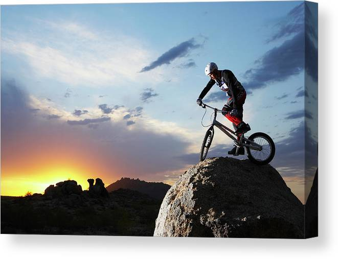 Sports Helmet Canvas Print featuring the photograph Bike Rider Balancing On Rock Boulder by Thomas Northcut