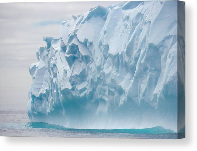 Scenics Canvas Print featuring the photograph Blue Iceberg Carved By Waves Floats In by Eastcott Momatiuk