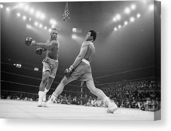 Joe Frazier Canvas Print featuring the photograph Boxer Ali Dodging A Punch From Frazier by Bettmann