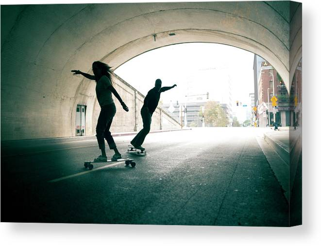Mature Adult Canvas Print featuring the photograph Couple Skateboarding Through Tunnel by Ian Logan