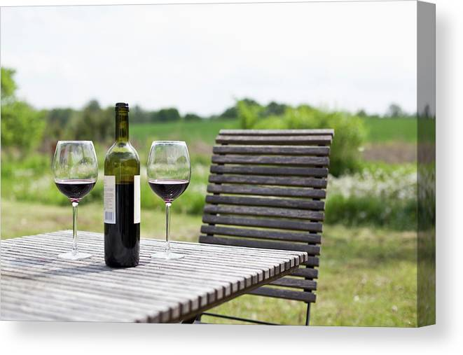 Five Objects Canvas Print featuring the photograph Glasses And A Bottle Of Red Wine On An by Halfdark