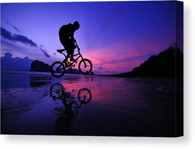 The Twilight Series Canvas Print featuring the photograph Silhouette Of A Mountain Biker On Beach by Primeimages