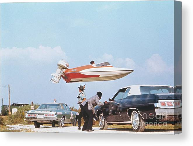 Event Canvas Print featuring the photograph Stuntman Jumping A Speedboat Over Cars by Bettmann