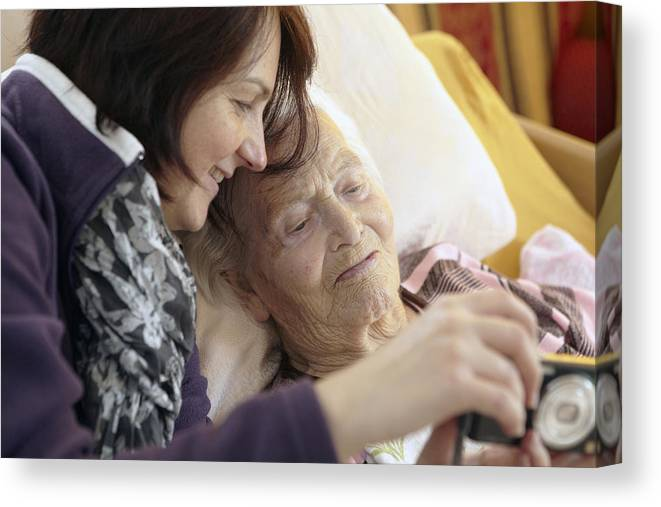 Mature Adult Canvas Print featuring the photograph Bedridden Grandmother With Granddaughter by Martin Leigh