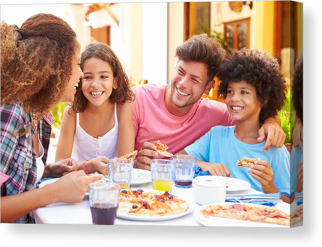 Child Canvas Print featuring the photograph Family gathered at an outdoor restaurant to share a meal by Monkeybusinessimages