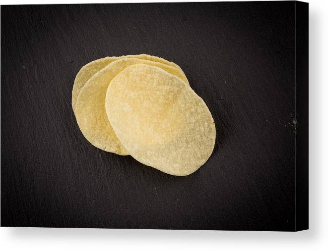 Black Color Canvas Print featuring the photograph Potato chips on a black by R.Tsubin