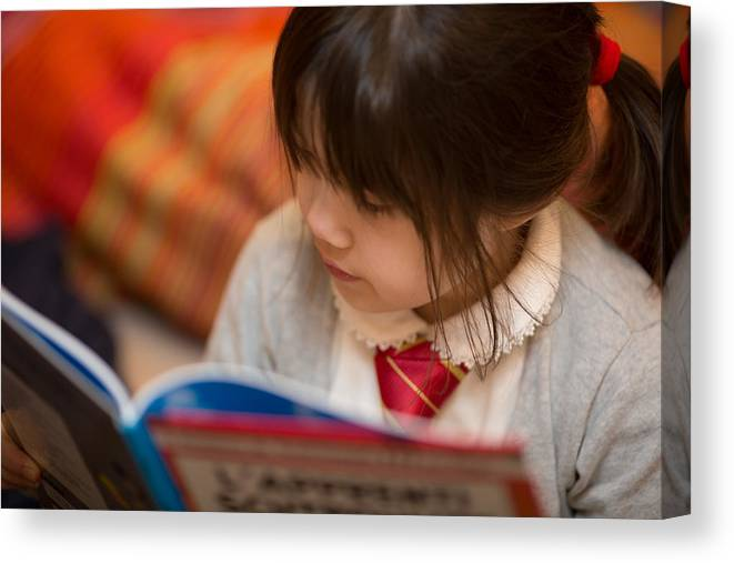 Child Canvas Print featuring the photograph Reading a book by Benoist SEBIRE