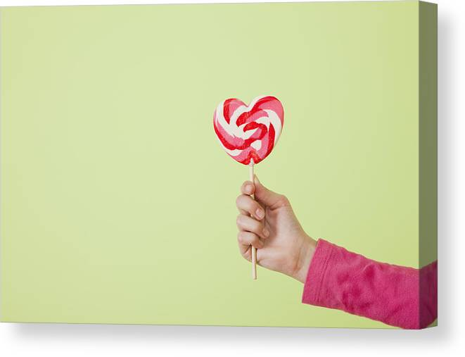 Child Canvas Print featuring the photograph Studio shot of girl's (10-11) hand holding heart-shaped lollipop by Vstock LLC