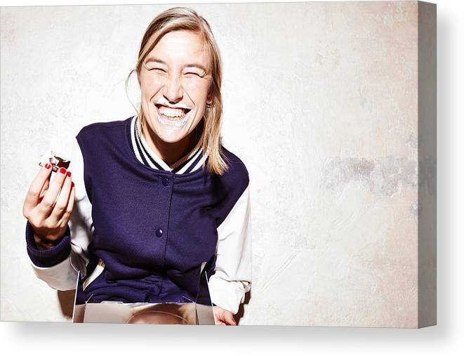 Unhealthy Eating Canvas Print featuring the photograph Studio shot of young woman eating chocolate marshmallows by Conny Marshaus