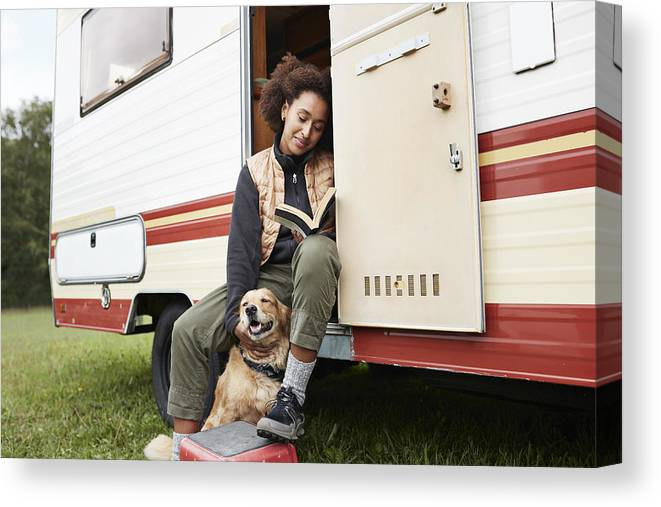 Pets Canvas Print featuring the photograph Woman with dog reading book in motor van by Klaus Vedfelt