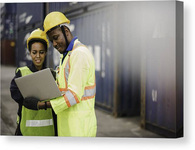 Working Canvas Print featuring the photograph Young African american men and woman worker Check and control loading freight Containers by use computer laptop at commercial shipping dock felling happy. Cargo freight ship import export concept by Niphon Khiawprommas