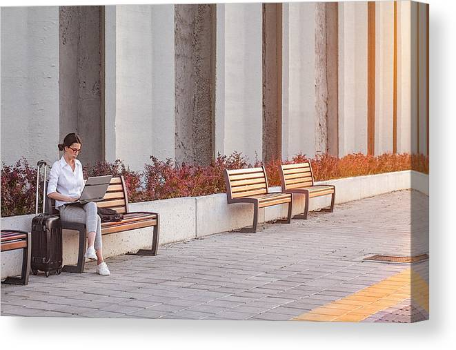 Internet Canvas Print featuring the photograph Young Businesswoman Working On A A Laptop While Sitting On A Bench On The City Street by Gruizza