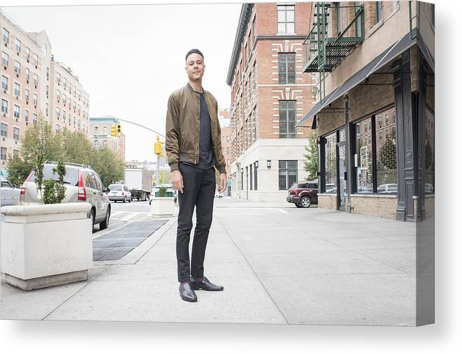 People Canvas Print featuring the photograph Young man standing on city sidewalk by Tony Anderson