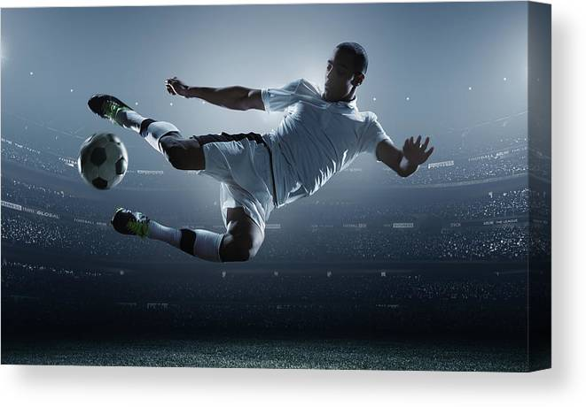 Goal Canvas Print featuring the photograph Soccer Player Kicking Ball In Stadium by Dmytro Aksonov