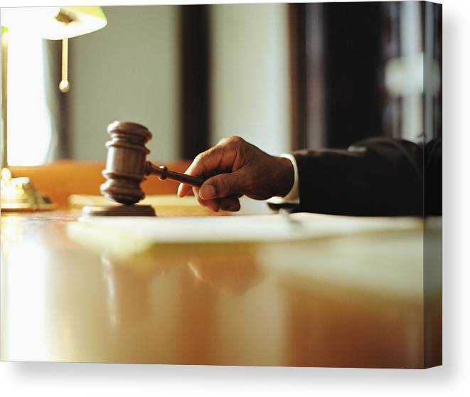 Punishment Canvas Print featuring the photograph Male judge striking gavel in courtroom, close-up by Yellow Dog Productions