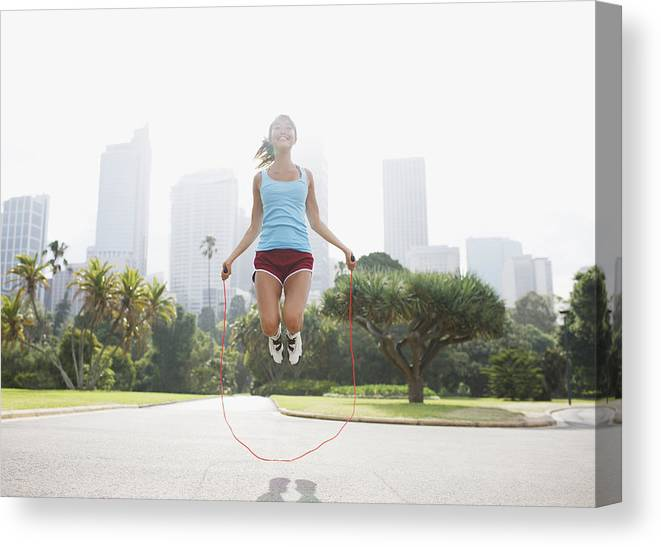 People Canvas Print featuring the photograph Woman skipping rope in park by Tom Merton