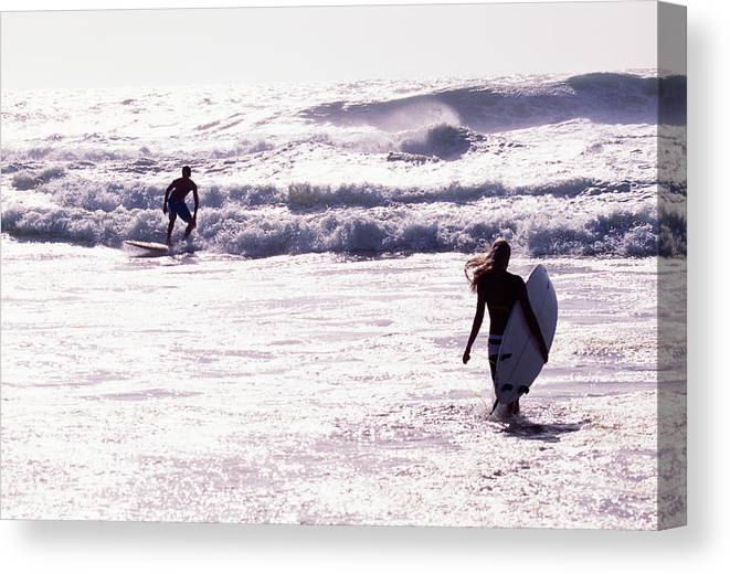 Wind Canvas Print featuring the photograph Man Surfing On Sea, Woman Walking With by Johner Images