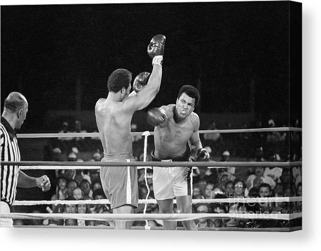 People Canvas Print featuring the photograph Muhammad Ali Punching George Foreman by Bettmann