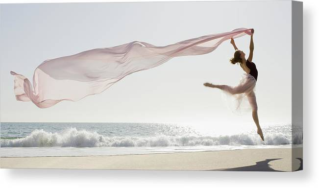 Ballet Dancer Canvas Print featuring the photograph Dancer Leaping On Beach by Tetra Images - Pt Images