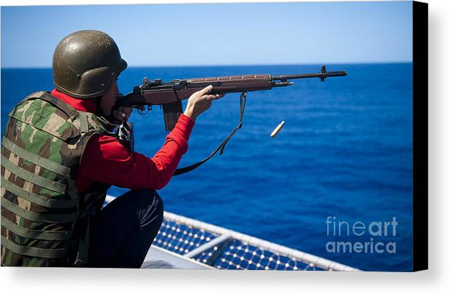 Shooting Canvas Print featuring the photograph Aviation Ordnanceman Fires An M-14 by Stocktrek Images