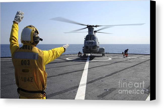Guidance Canvas Print featuring the photograph Boatswain's Mate Directs A Ch-46 Sea by Stocktrek Images