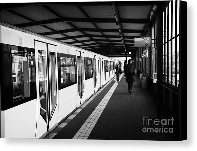 Berlin Canvas Print featuring the photograph modern yellow u-bahn train sitting at station platform Berlin Germany by Joe Fox