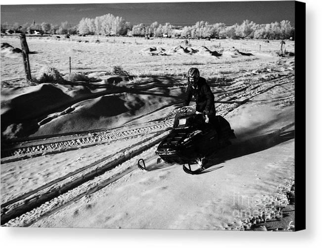 Man Canvas Print featuring the photograph man on snowmobile crossing frozen fields in rural Forget Saskatchewan Canada by Joe Fox