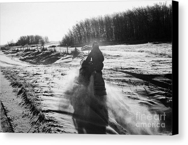Man Canvas Print featuring the photograph man on snowmobile crossing frozen fields in rural Forget Saskatchewan Canada by Joe Fox