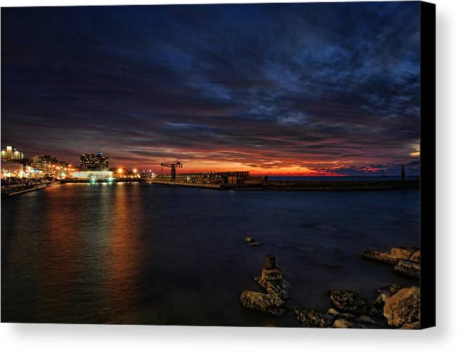 Israel Canvas Print featuring the photograph a flaming sunset at Tel Aviv port by Ron Shoshani