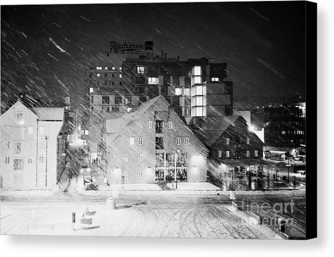 Looking Canvas Print featuring the photograph looking out atTromso bryggen quay harbour on a cold snowy winter night troms Norway europe by Joe Fox