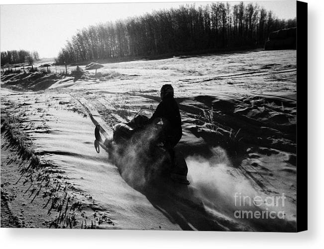 Man Canvas Print featuring the photograph man on snowmobile crossing frozen fields in rural Forget canada by Joe Fox