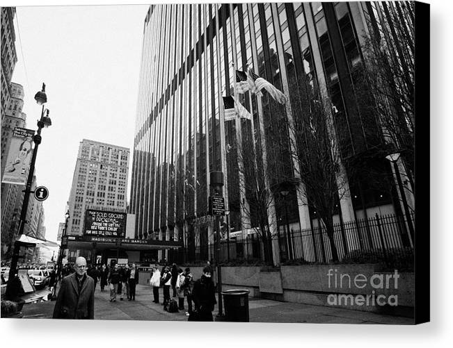 Usa Canvas Print featuring the photograph people on the sidewalk outside madison square garden with US flags flying new york city by Joe Fox