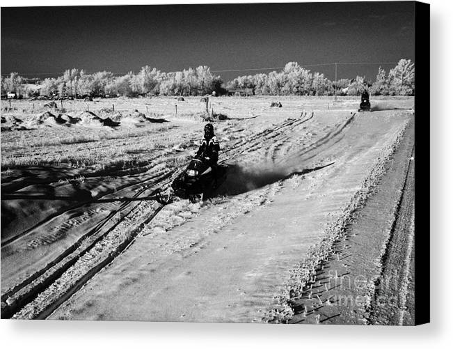 Man Canvas Print featuring the photograph two men on snowmobiles crossing frozen fields in rural Forget Saskatchewan Canada by Joe Fox