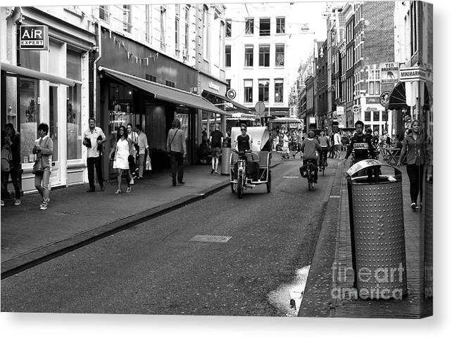 Street Riding In Amsterdam Canvas Print featuring the photograph Street Riding In Amsterdam Mono by John Rizzuto